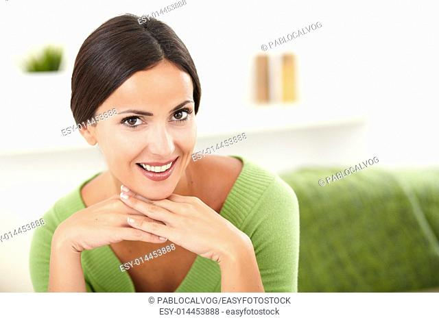 Beautiful woman in green shirt contemplating while looking at the camera - copy space
