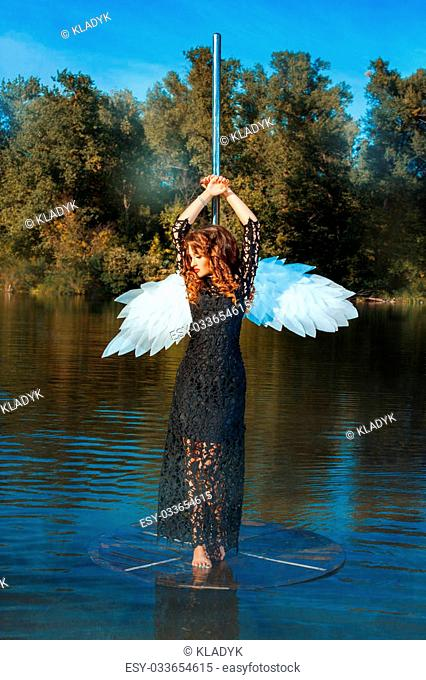 Girl with angel wings standing near a pole dance. This occurs in the open air on a river