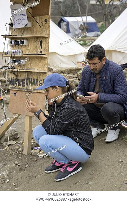 Refugees from Syria and Afghanistan charging their mobile phones at the Greek island of Lesbos wait to be transferred to Athens by sea