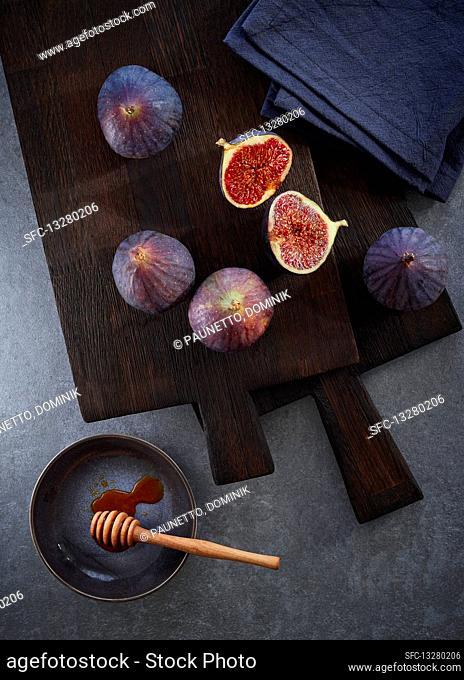 Fresh figs on a dark cutting board with a honey dipper