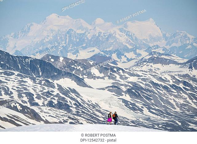 Couple walking on a mountain top with the massive mountains of Kluane National Park and Reserve looming in the distance; Haines Junction, Yukon, Canada