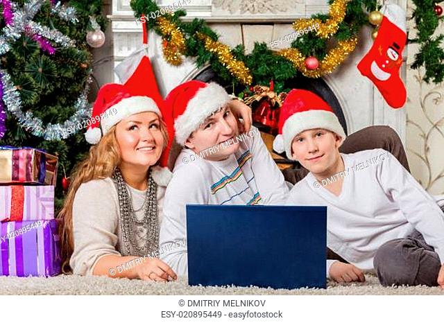Family with notebook near Christmas tree