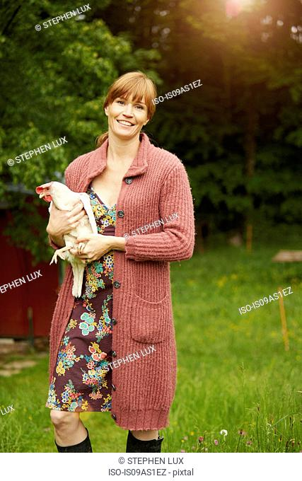 Portrait of woman in field holding hen