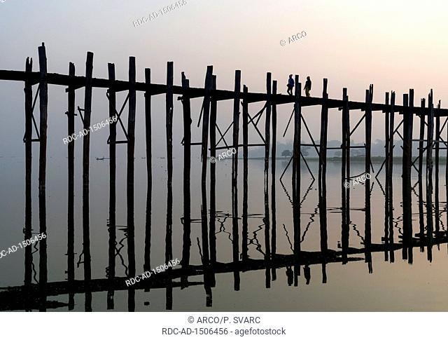 People walk U Bein Bridge across Taungthaman Lake in Amarapura near Mandalay, Burma, Myanmar