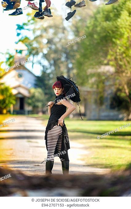 A pretty 23 year old red headed woman holding a black umbrella and wearing a black dress and striped stockings looking down from the camera, outdoors