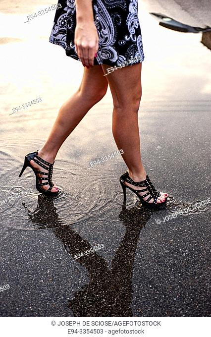 Partial view of a woman's bare legs walking on the street
