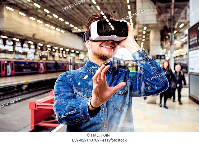 Hipster man in denim shirt wearing virtual reality goggles, standing at train station