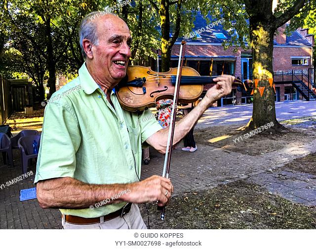 Tilburg, Netherlands. Senior violin player performing his music during a neighborhood summer party