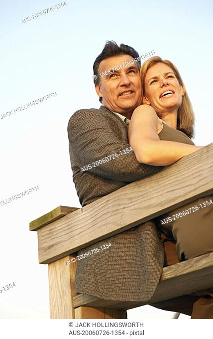 Low angle view of a mid adult woman and a mature man sitting by a railing