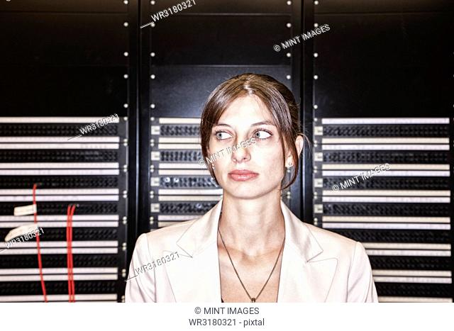 Portrait of female technician working in a large computer server room