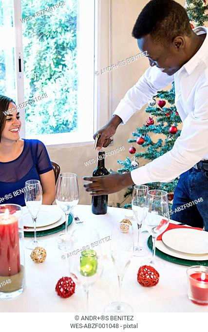 Man opening a bottle of wine at Christmas dinner
