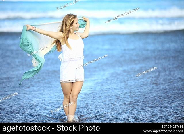 A lady with pareo walking on a coast. Horizontal outdoors shot