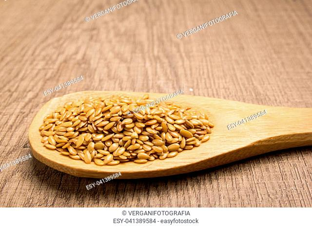 Linum usitatissimum is scientific name of Golden Flax seed. Also known as Linseed, Flaxseed and Common Flax. Grains in wooden spoon. Rustic