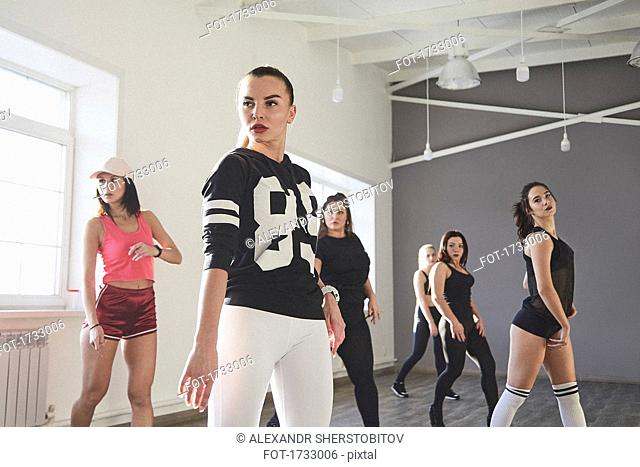 Confident female friends dancing while practicing in dance studio