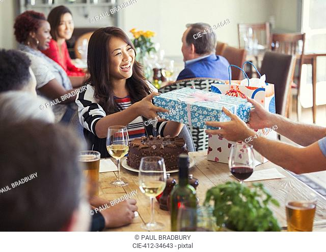 Smiling woman receiving birthday gift from friend at restaurant table