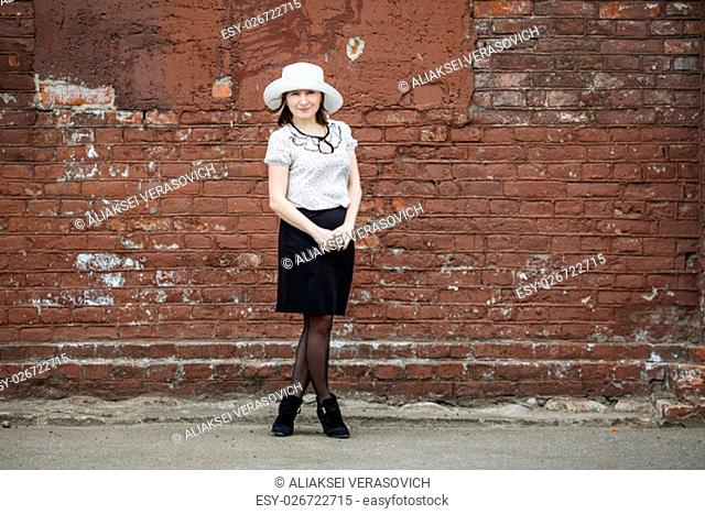 Photo of a woman in a white hat, blouse and black skirt, standing against the backdrop of an old vintage brown brick wall. Space for text