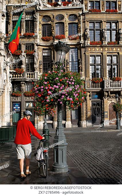 A cyclist and background buildings Louve, Sac and Brouette. Grand Place, Brussels, Belgium. The Louve, Sac and Brouette are a group of houses that were not...