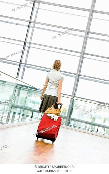 Woman dragging a suitcase