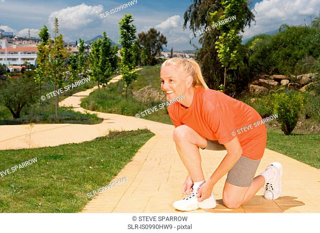 Mature woman runner tying shoelaces