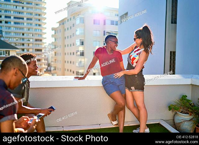 Happy friends hanging out on sunny urban rooftop balcony