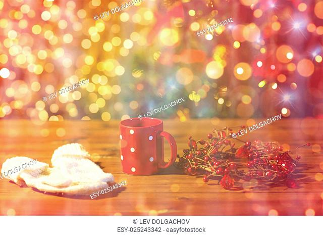 holidays, christmas, winter and drinks concept - close up of tea cup with mittens and christmas decoration on wooden table over lights