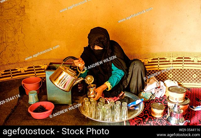 A woman in traditional costume makes mint tea at a small remote village in the Draa Valley, Southern Morocco, Africa