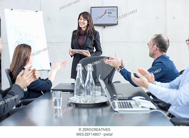 Colleagues applauding for businesswoman leading a presentation