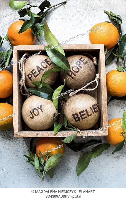 Overhead view of Christmas decorations in wood box surrounded by citrus fruit