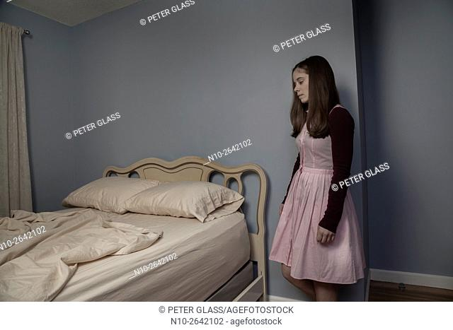 Young woman standing next to an empty bed
