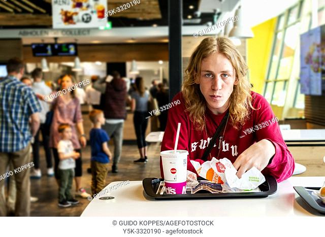 Berlin, Germany. Young adult, male music student eating an unhealthy set of hamburgers at the McDonalds fastfood restaurant during his lunchbreak