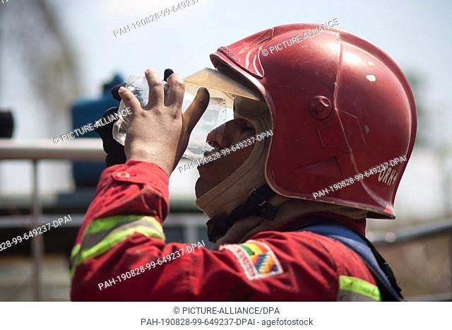 28 August 2019, Bolivia, Santa Rosa de Tucabaca: A member of the fire brigade drinks water during a mission. The emergency forces in eastern Bolivia continue to...