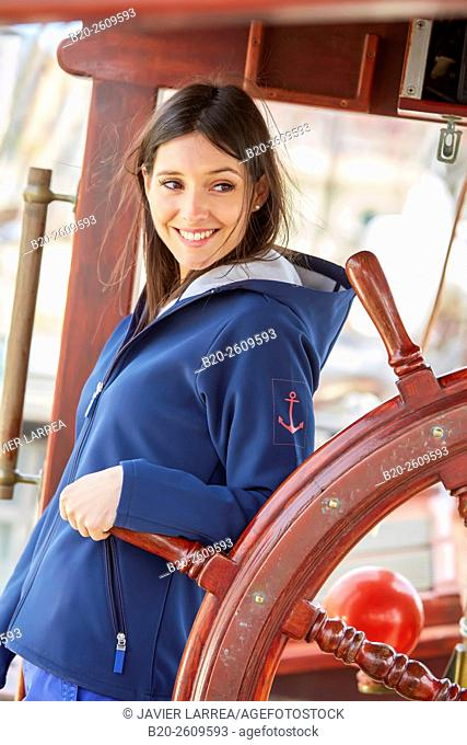 Young woman woman at the helm of a sailboat, galleon. Basque Country. Spain