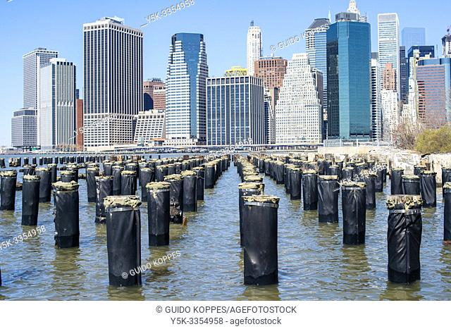 New York City, USA. View on the remains of a harbor pier and the Skyline of down town Manhattan from Brooklyn Bridge Park / Pier 1