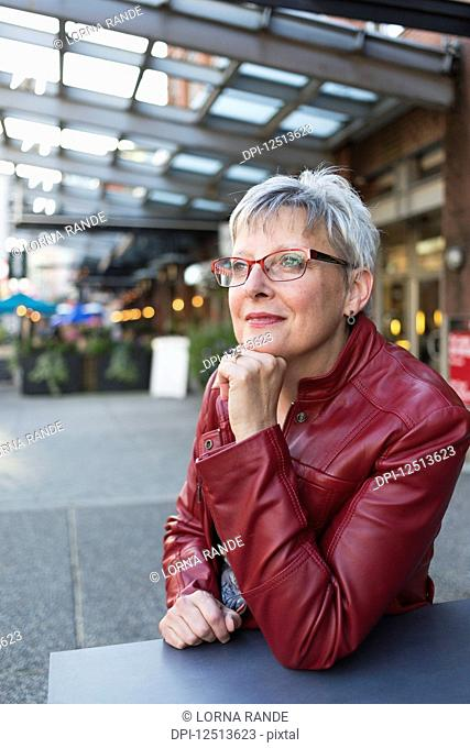 Portrait of a mature woman in a red leather jacket sitting at a table outside a shop with her chin resting in her hand; Vancouver, British Columbia, Canada