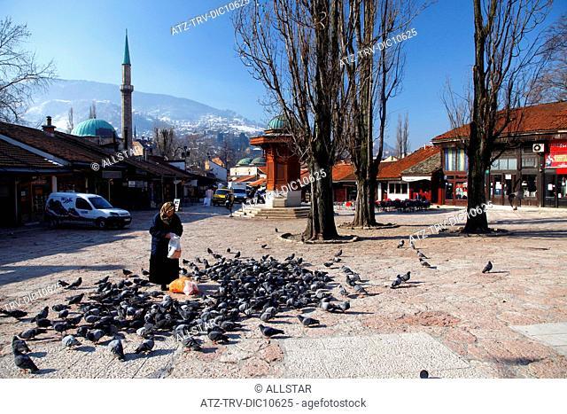 OLD WOMAN FEEDING PIGEONS AT SEBILJ FOUNTAIN; BASCARSIJA MARKET, OLD TOWN, SARAJEVO, BOSNIA; 16/03/2010