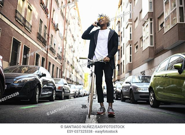 Handsome young man using mobile phone and fixed gear bicycle in the street