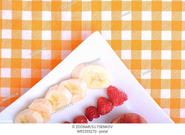 peach raspberries bananas close up as health food concept