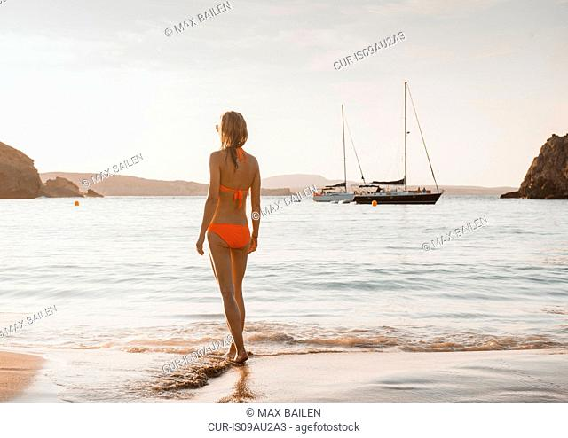 Woman wearing bikini looking out from beach, Menorca, Balearic islands, Spain