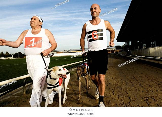 Two men in sportswear running on a racetrack with two greyhounds on leads