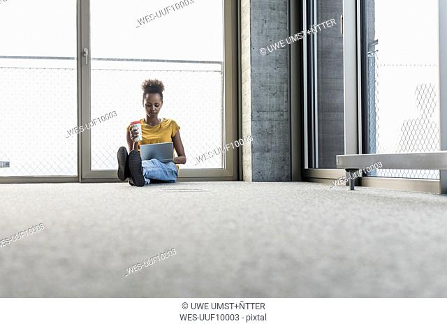 Young woman sitting on floor using laptop