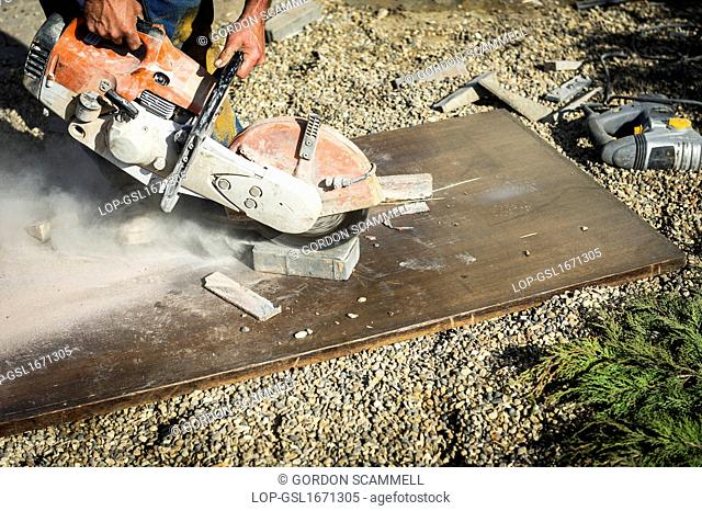 England, Essex, Basildon. A worker using a disc cutter to cut a paving block