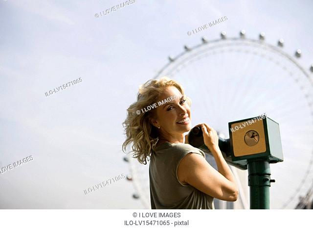 A middle-aged woman using a telescope in front of the London Eye