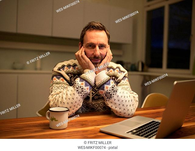 Portrait of casual businessman with laptop on table at home