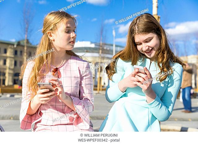 Russia, Moscow, teenage girls with smartphones