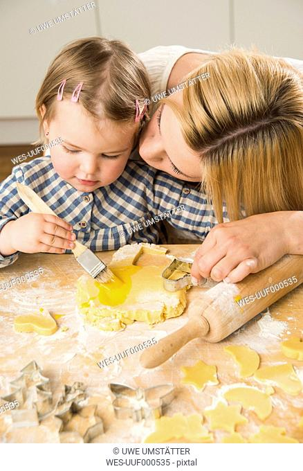 Mother and daughter baking in kitchen at home