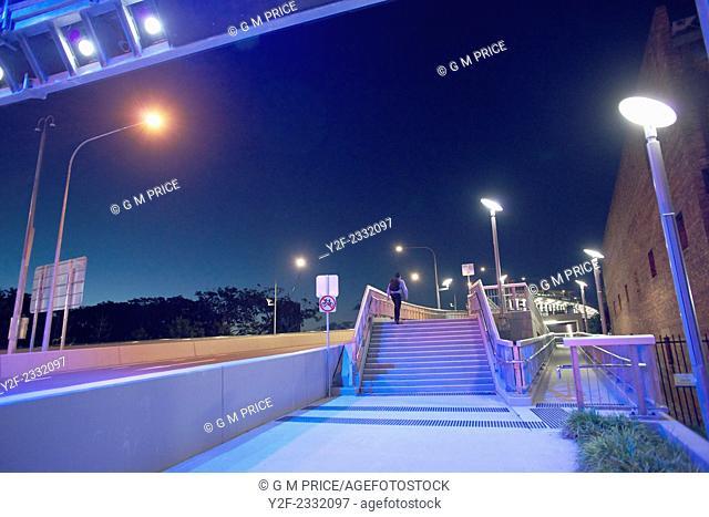 man walking at night under motorway lights, Brisbane