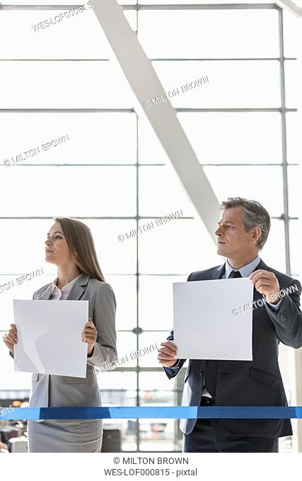 Woman and man holding blank papers at the airport