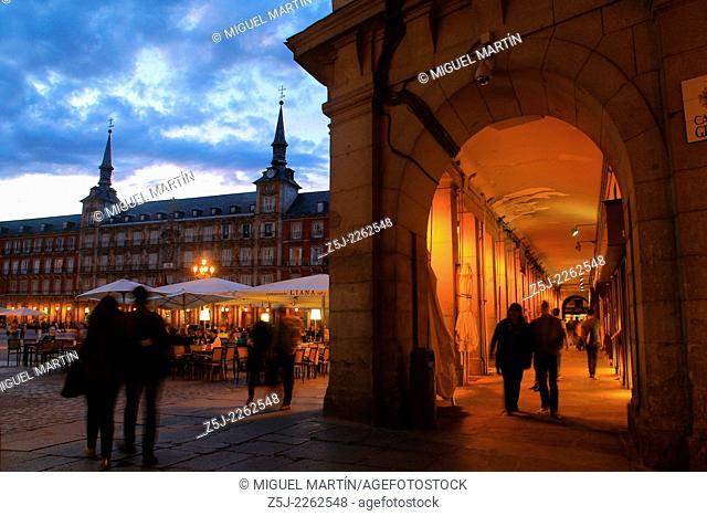 Cloudy twilight on the Plaza Mayor of Madrid seen from Gerona street next to some of many restaurants placed under the porticoes facing the square