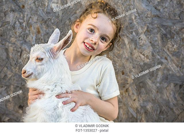 Portrait of cute girl holding baby goat outdoors