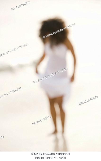 Defocused image of Hispanic woman at beach
